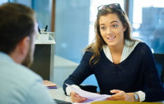 stock-photo-80124087-young-female-office-worker-chatting-to-a-colleague